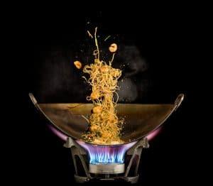 Traditionele plaatstalen wokpan op hoog vuur